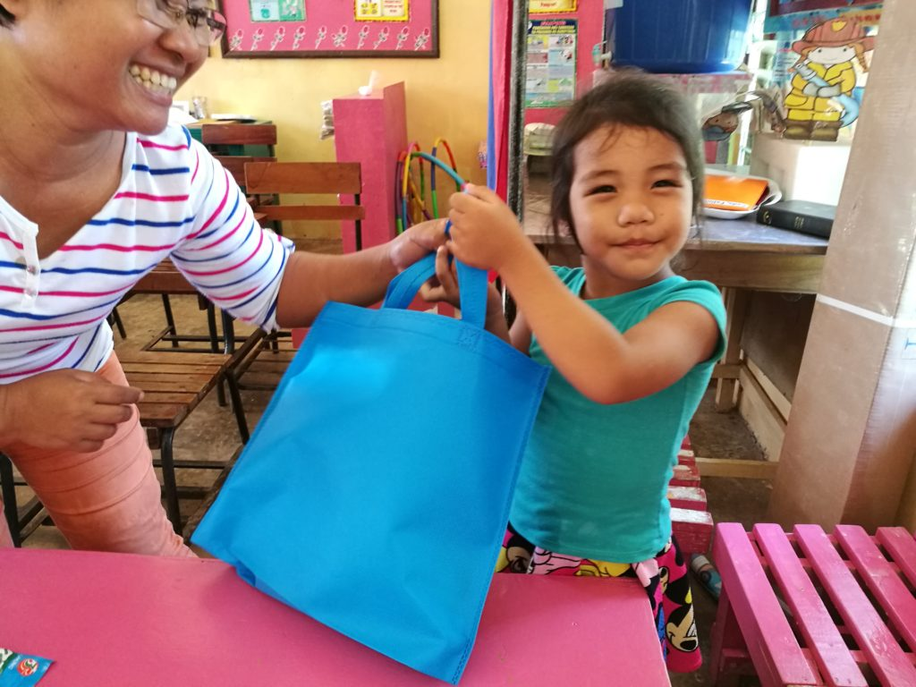 kid in bayobay elementary school given a bag full of school supplies